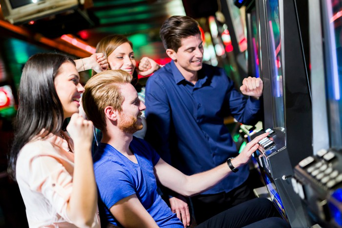 Group of friends playing video arcade game