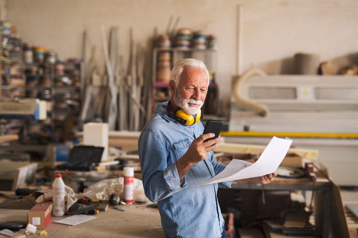 Older person holding document and looking at phone in workshop.