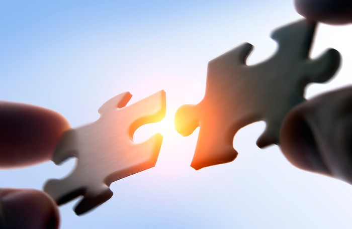 Fingers holding two jigsaw puzzle pieces close to each other and ready to lock into place.