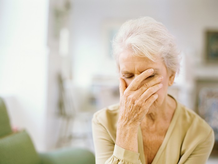 A senior woman buries her face in her palm out of frustration.