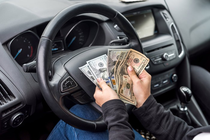 A pair of hands holds money in front of a car's steering wheel.