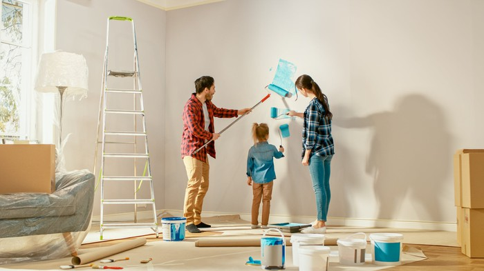 Parents showing their young daughter how to paint a wall with a roller.