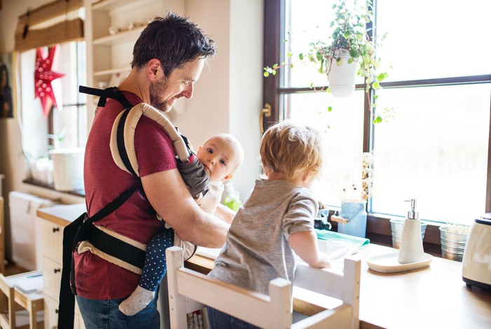 A man with a baby strapped to his front doing dishes with a toddler assisting
