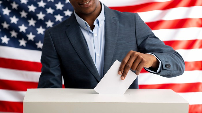 A voter inserts a ballot in the voting box in front of an American flag.