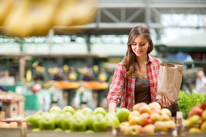 Woman in the produce aisle of a supermarket, with apples displayed in the foreground