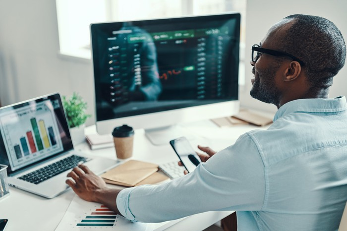 A man with trading screens up on his laptop and desktop computers, making trades.