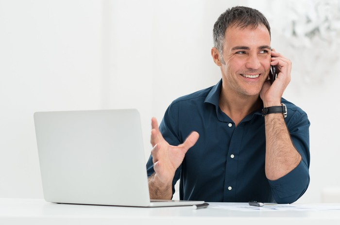 Smiling man at laptop talking on phone