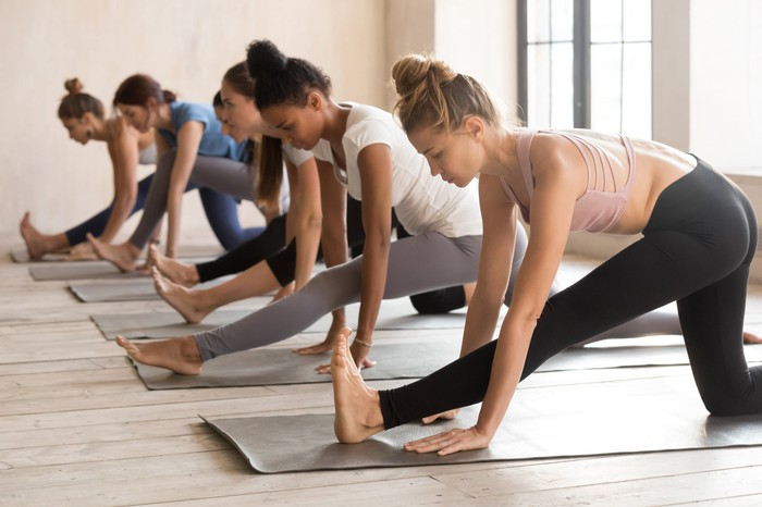 Young women performing yoga while dressed in athleisure wear.