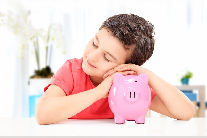 A smiling child with his head and hands on a piggy bank.