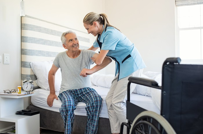 Woman in scrubs helping an older man out of bed