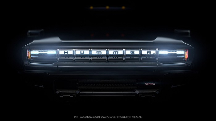Grill of GM Hummer electric vehicle, with lights lit and the rest dark.