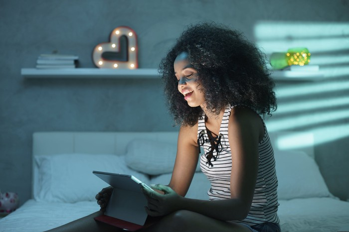 Smiling young women sitting on a bed watching streaming video on a tablet at night.