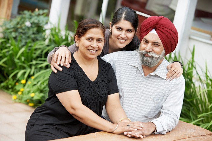 A sikh family is shown -- middle-aged parents and a young adult daughter.