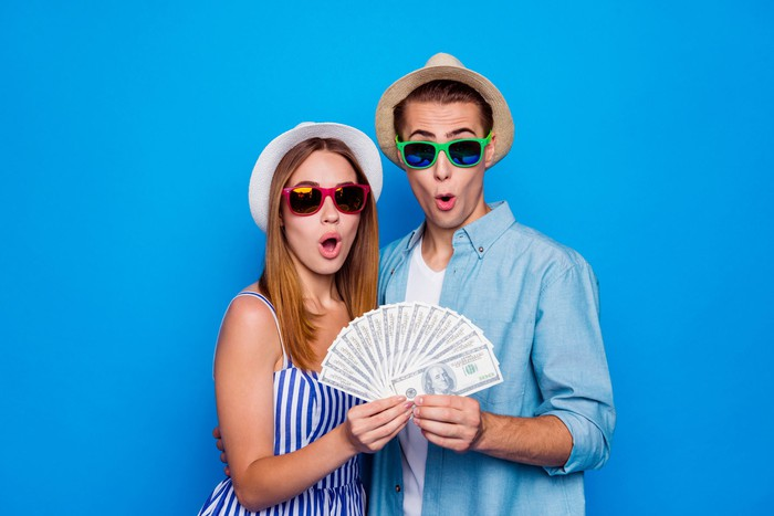Two cheerfully amazed people in cap holding in hands large sum of money isolated on blue color background.