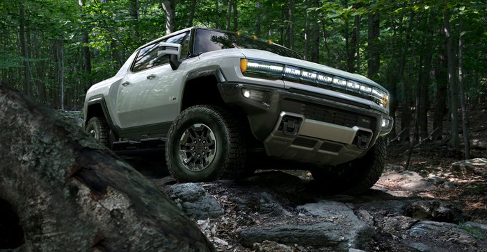 A silver GMC Hummer EV, shown on a rocky trail.