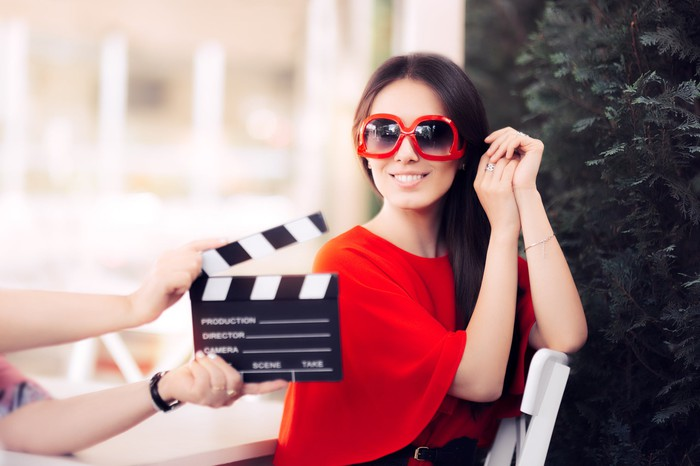 An actress in a red dress and oversized glasses smiles behind the film crew's clapper.