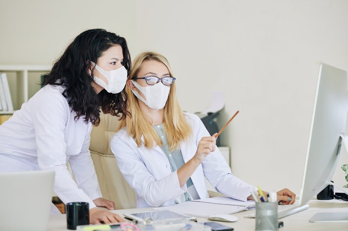 Two healthcare professionals wearing face masks, looking at a PC monitor