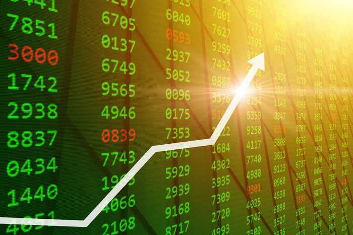 A white arrow pointing up across a green stock market screen filled with green and red numbers