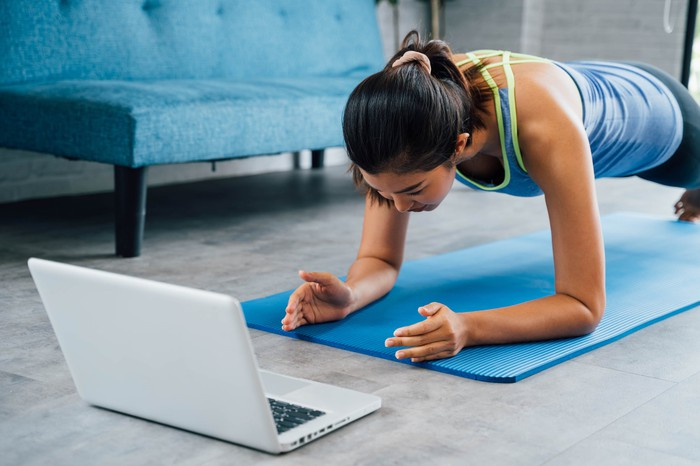 Woman doing push-ups on elbows on yoga mat while looking at a laptop screen.
