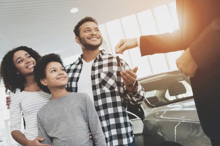 family being handed keys by car dealer in showroom