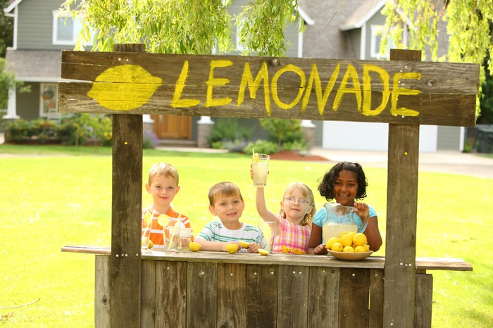 Four kids at a lemonade stand in the front yard.
