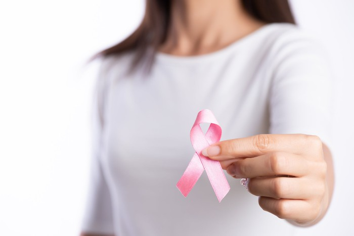 A lady holding a pink ribbon forward signifying breast cancer awareness.