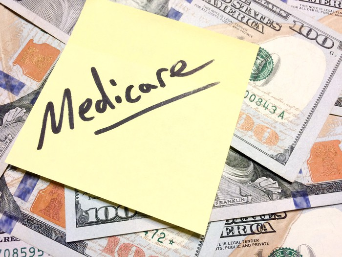 Sticky note with the word Medicare on top of a pile of bills