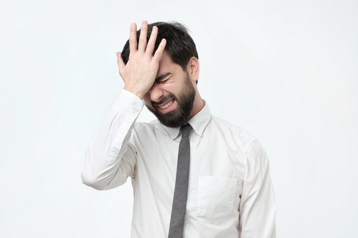 Man in dress shirt and tie smacking his head