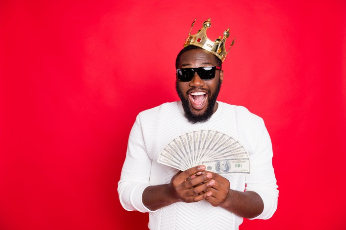 Man in sunglasses and white sweater wearing a crown and fanning out a stack of money in his hands, all against a red background.