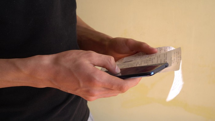 Man holding receipts and smartphone
