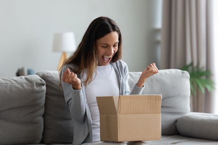 Excited woman opening a box