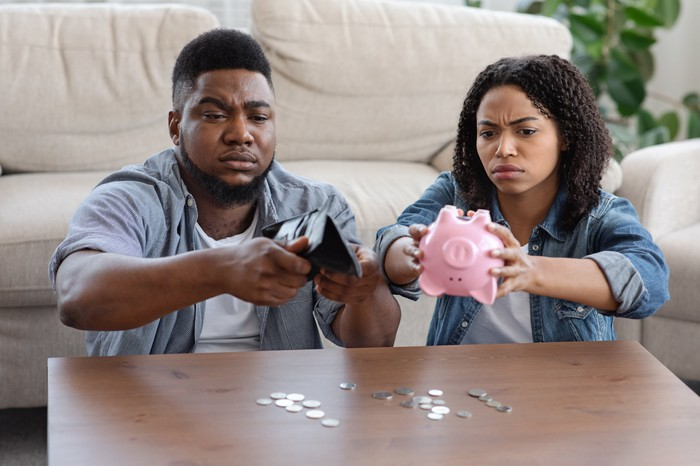 Couple sitting at coffee table, emptying their piggy banks.