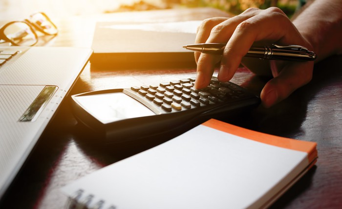 Person typing on calculator with pen in hand
