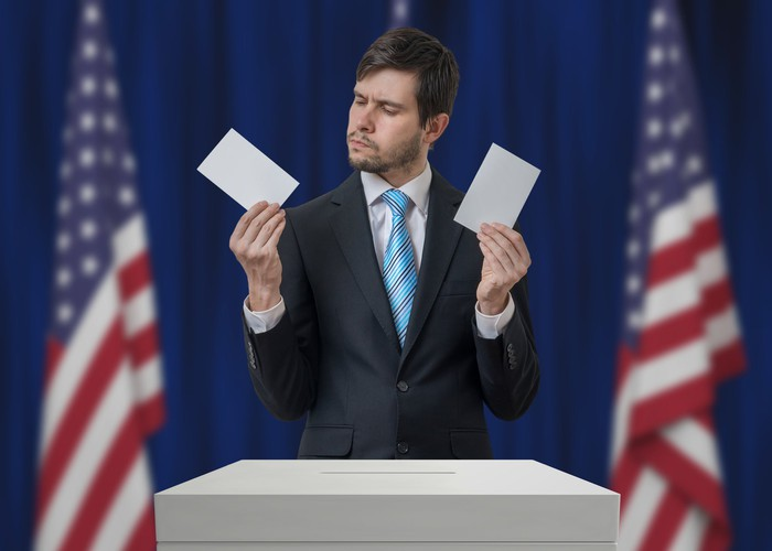 A man in a suit at an election box holding two ballots, trying to decide which one to cast.