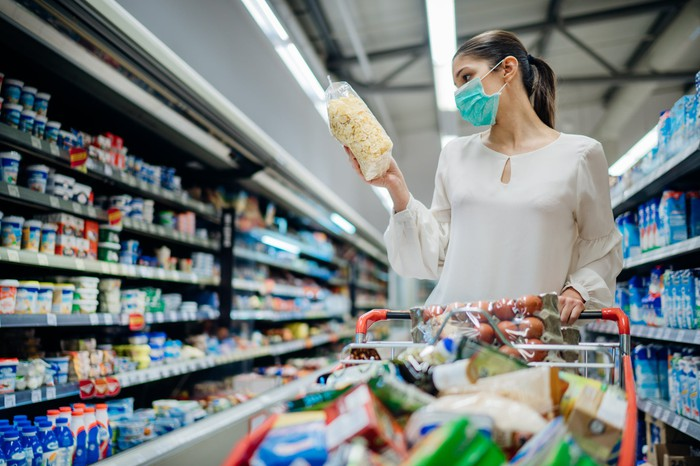 A mask-wearing woman in the aisle of a store. She is holding an item and her cart is full.