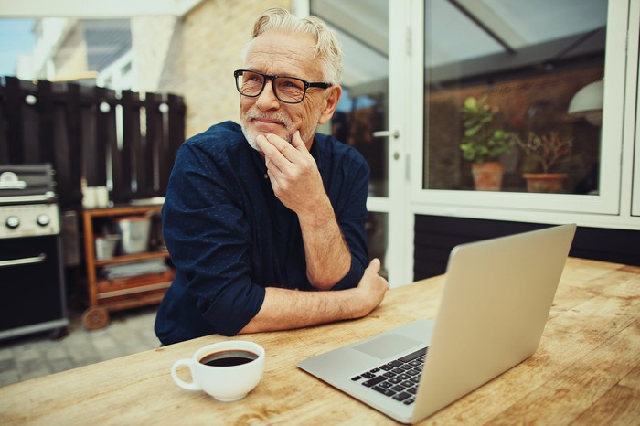 Smiling older man at table with laptop and mug of coffee