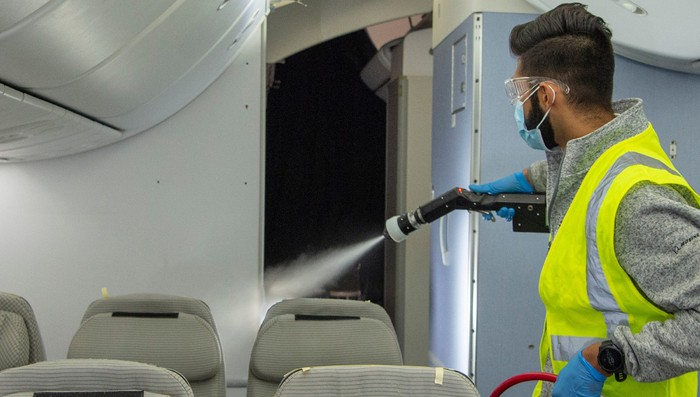 A person wearing a mask spraying aerosol disinfectant on a plane.