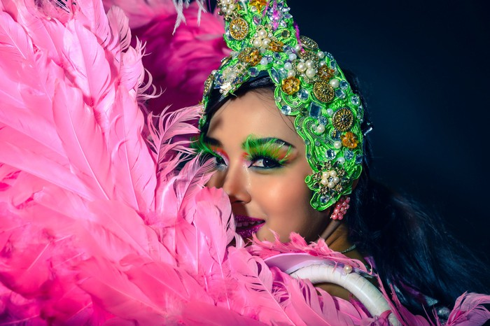 """A Las Vegas cabaret showgirl looking out from behind pink feathered """"wings,"""" wearing a green and white headdress."""