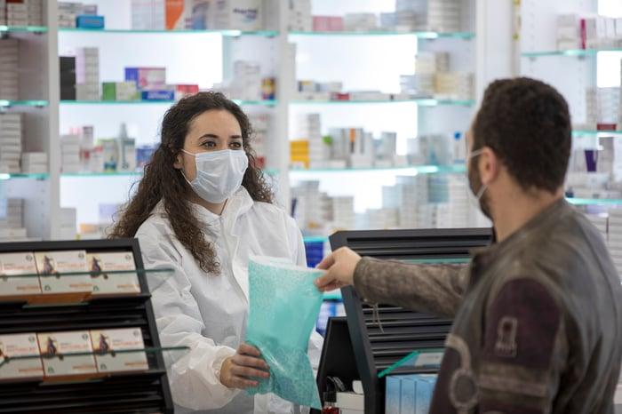 Pharmacist wearing mask and handing customer a prescription