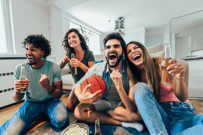 A group of basketball fans sitting in a room drinking beer, eating popcorn, and watching sports