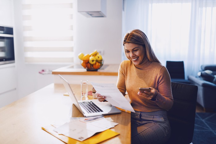 Woman in kitchen with papers, laptop, and calculator