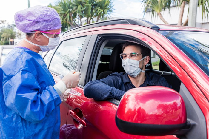 A man in his car talks to a doctor as she prepares a nasal swab for a COVID-19 test.