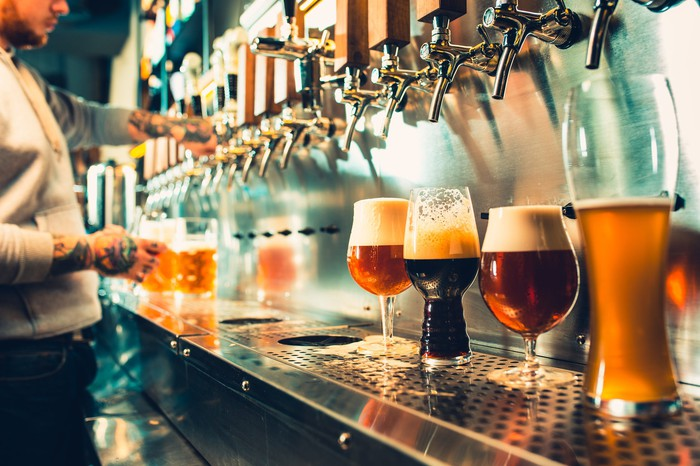 A bartender pours a line of craft beers on tap