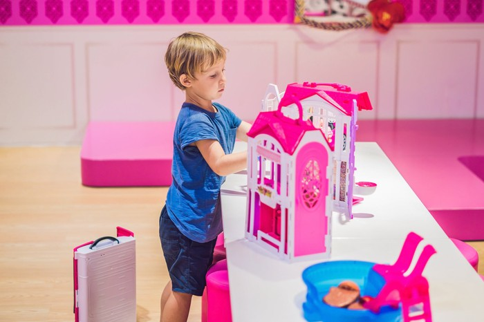 Child playing with toy house.