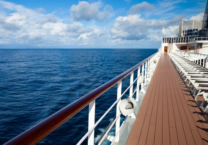 A long line of empty deck chairs along the empty deck of a cruise ship on a sunny day.