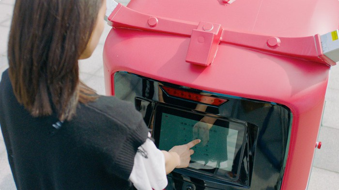 A woman presses a touch screen on a delivery robot.