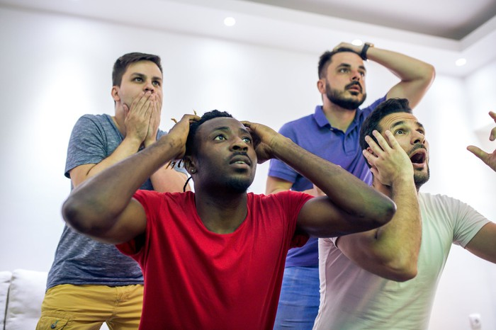 A group of male sports enthusiasts watching a game.