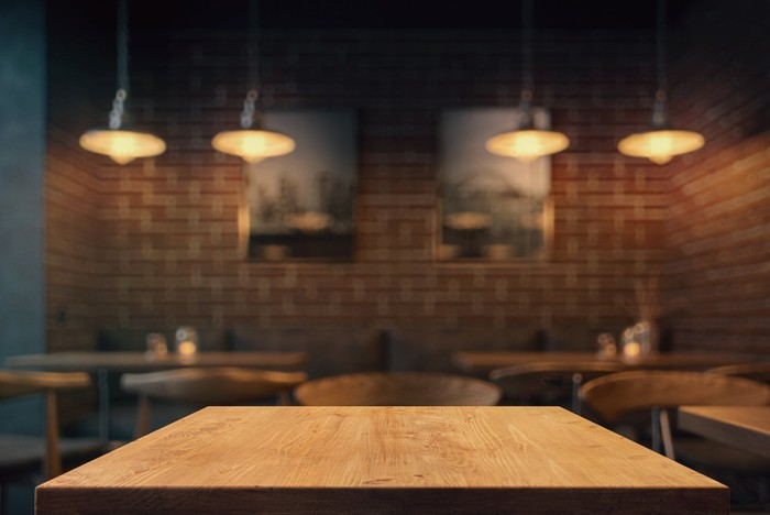 empty restaurant table with brick wall in background