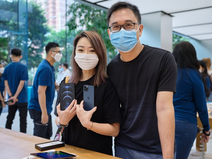 Customer holding an iPhone 12 Pro at launch in an Apple Store
