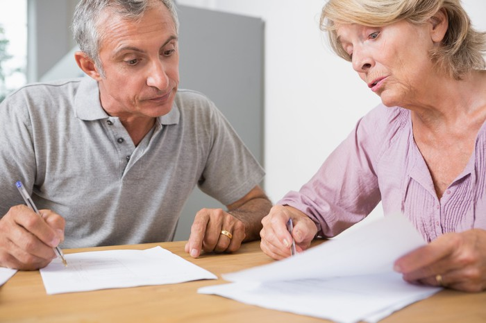 Older man and woman holding pens to documents